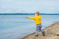 Pierres de lancement de jeune garçon en eau de mer Photo libre de droits
