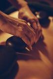 Pierres de Placing Hot de masseuse sur le dos d'une femme Photographie stock libre de droits