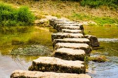 Pierres de progression traversant une petite rivière image stock