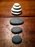 Pierres de zen sur une table antique superficielle par les agents photos stock