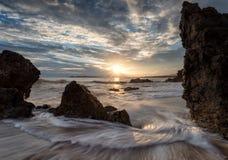 Pierres en eau de mer sur le fond de coucher du soleil Image libre de droits