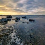 Pierres et glace sur la côte, printemps Photographie stock libre de droits