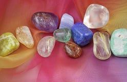 Pierres gemmes de Chakra sur la mousseline de soie d'arc-en-ciel Photographie stock