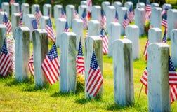 Pierres graves avec les drapeaux américains dans un cimetière militaire Images libres de droits