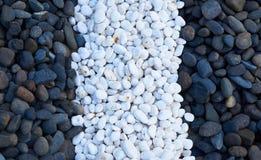 Pierres noires et blanches étendues dans les rangées Photographie stock