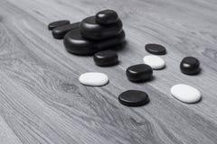 Pierres noires et blanches de massage sur le conseil gris Images libres de droits