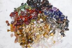 Pierres semi-précieuses colorées sur le fond de marbre, texture photographie stock libre de droits