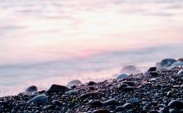 Pierres sur l'eau de Pebble Beach et de mer au coucher du soleil Fond Tir diagonal image libre de droits