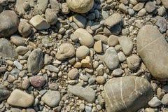 Pierres sur le rivage de lac à la couleur brune photographie stock