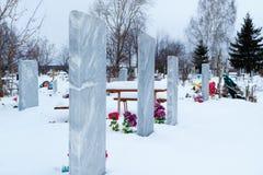 Pierres tombales dans le vieux cimetière de village en hiver en Russie images stock