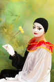 Pierrot clown with flower. Beautiful Pierrot clown holding a flower and smiling Royalty Free Stock Photo