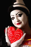 Pierrot in love. Beautiful pierrot clown in love with a red candy heart Royalty Free Stock Photo
