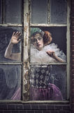 A pierrot woman behind the glass Stock Images