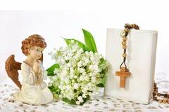 Pierwszy Świętej komuni wciąż życie z aniołem, różanem i lelują t, obraz stock