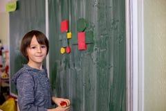 Pierwszy stopnia dziecko, uczy się matematykę, kształtuje i barwi przy szkołą fotografia stock