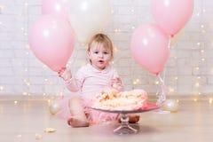 Pierwszy urodzinowy świętowanie - śmieszna mała dziewczynka z roztrzaskującym tortem Fotografia Stock