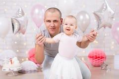 Pierwszy urodzinowy pojęcie - śliczna mała dziewczynka i ojciec w dekorującym pokoju z tortem i balonami obrazy stock