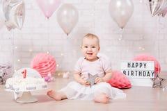Pierwszy urodzinowy pojęcie śmieszna brudna dziewczyna i roztrzaskujący urodzinowy tort z - światłami i balonami obraz stock