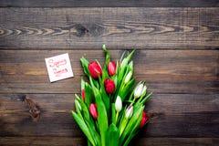 pierwszy wiosenny kwiat Bukiet kolorowi tulipany blisko wiosny przychodzi notatkę na ciemnej drewnianej tło odgórnego widoku kopi Obraz Stock