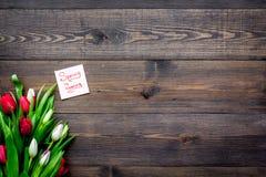 pierwszy wiosenny kwiat Bukiet kolorowi tulipany blisko wiosny przychodzi notatkę na ciemnej drewnianej tło odgórnego widoku kopi Zdjęcia Stock