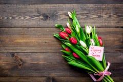 pierwszy wiosenny kwiat Bukiet kolorowi tulipany blisko wiosny przychodzi notatkę na ciemnej drewnianej tło odgórnego widoku kopi Obraz Royalty Free