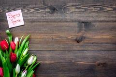 pierwszy wiosenny kwiat Bukiet kolorowi tulipany blisko wiosny przychodzi notatkę na ciemnej drewnianej tło odgórnego widoku kopi Fotografia Stock