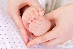 Pies 2 del bebé de la explotación agrícola de la madre Imagen de archivo libre de regalías