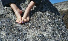 Pies adolescentes de la muchacha en la roca Imagen de archivo libre de regalías
