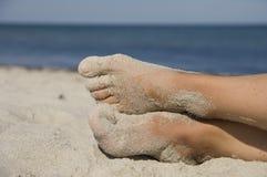 Pies arenosos de las muchachas en la playa Imágenes de archivo libres de regalías