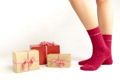 Pies atractivos de la mujer de Papá Noel Concepto de las compras de la Navidad Caja de regalo de Navidad Imagen de archivo