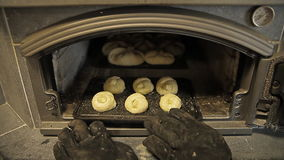 The pies on a baking tray are put into the furnace for baking stock video