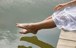 Pies blandos del ` s de las mujeres en la orilla del río Foto de archivo libre de regalías