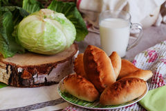 Pies cabbage and jug of milk still life with a Royalty Free Stock Image