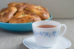 Pies with cabbage and tea. Homemade pies with cabbage on a plate and a hot cup of tea stock images