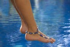 Pies con la pulsera de tobillo sobre la piscina Fotografía de archivo