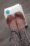 Pies con los calcetines de las lanas y el calentador eléctrico foto de archivo libre de regalías