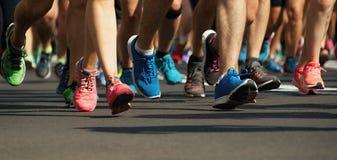 Pies corrientes de la gente de la raza del maratón en el camino de ciudad