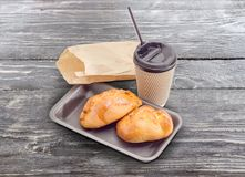 Pies with cottage cheese and tea in paper cup. Two sweet pies with cottage cheese toppings on a foam food container, tea in the disposable paper cup with plastic Stock Image