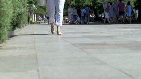 Pies de gente que camina a lo largo de la 'promenade' de Yalta en un día de verano soleado 4k metrajes