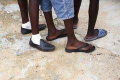 Pies de hombres africanos en diversos zapatos Imágenes de archivo libres de regalías