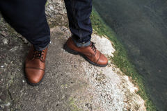 Pies de hombres en vaqueros del orillo y zapatos retros Imagen de archivo libre de regalías