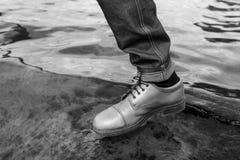 Pies de hombres en vaqueros del orillo y zapatos retros Foto de archivo libre de regalías