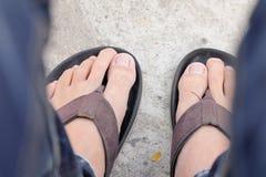 Pies de hombres que llevan las sandalias negras Fotografía de archivo
