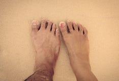 pies de hombres y de mujeres en el arena de mar Fotos de archivo
