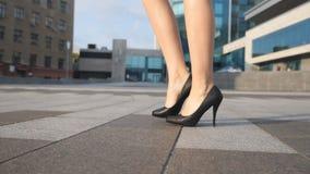 Pies de la empresaria joven en calzado en entrar de tacón alto en calle urbana Piernas femeninas delgadas en zapatos negros en al almacen de metraje de vídeo