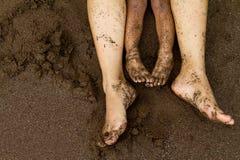 Pies de la familia en la arena de la playa Foto de archivo libre de regalías