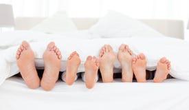Pies de la familia en la cama Imágenes de archivo libres de regalías