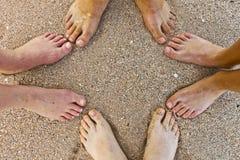Pies de la familia en la playa foto de archivo