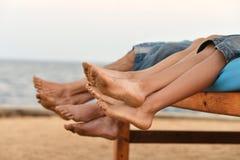 Pies de la familia en la playa Fotos de archivo