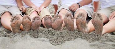 Pies de la familia en la playa en línea Imagenes de archivo